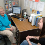 INCENTIVES, both positive and negative, have convinced URI nursing professor Debby Godfrey Brown that she should retire now; here she talks with student Lauren Salerno. /