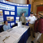 The Rotunda of the R.I. State House in Providence was the site of the 16th annual Celebrate South County, on May 13, which drew exhibits from more than 30 organizations. Here, staffers from the USS Saratoga Museum Foundation advocate for legislative action they say would loosen red tape, allowing the museum to make progress on its plans. /
