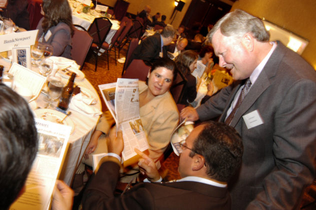Honorees from BankNewport, a winner in the Large Category, as they read the PBN Best Places To Work supplement. / PBN Photo/Frank Mullin