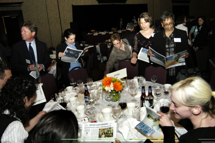 Honorees from KPMG LLP, a winner in the Medium Category, peruse the Best Places To Work supplement. / PBN Photo/Frank Mullin