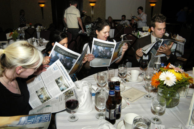 Guests take time to look for their winning company profile in the Best Places To Work supplement. / PBN Photo/Frank Mullin