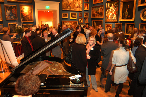 Guests enjoy the musical stylings of Lois Vaughn, on piano, as they peruse the Museum's main gallery. / PBN Photo/Frank Mullin