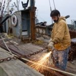 SALVAGE JOB: Fisherman Wayne Frye Jr. tries to salvage what he can from his derelict boat in New Bedford. /