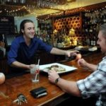 STAY A WHILE: Amalfi bartender Nathan Wallace serves dinner to customer Ken Tetzner at the Narragansett restaurant. /