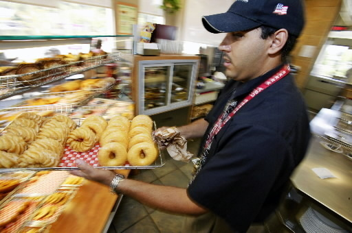 AN EMPLOYEE at a Tim Hortons shop in Connecticut puts out fresh doughnuts. /