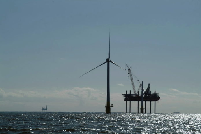 AN INSTALLATION VESSEL erects an offshore wind turbine in waters off the United Kingdom last summer. Deepwater Wind hopes to do the same off Rhode Island. /