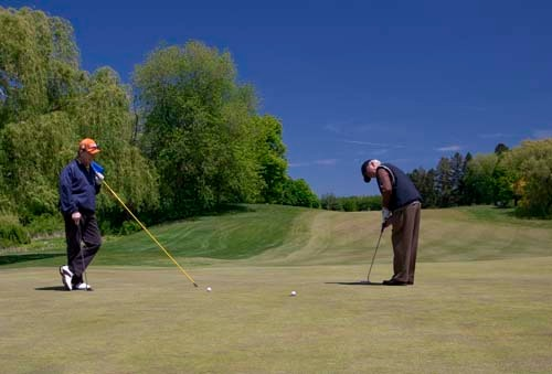 SEEING GREEN? Paul Trainor, right, plays a round of golf with Dan Pilkington at Metacomet Country Club in East Providence. Club leadership says that a lack of costly amenities allowed it to weather economic troubles experienced by other clubs. /