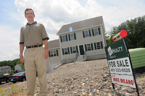 TOM MCNULTY, President of McNulty Real Estate, in front of a Cumberland home he is marketing. Rhode Island Association of Realtors second-quarter statistics show home sales increased in the period. /