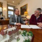 MODEL OF CONSISTENCY: The Preservation Society of Newport County Director of Finance Jim Burress, left, discusses budget plans with Accounting Manager Hugh M. Collard. A model of The Breakers mansion is in the foreground. /