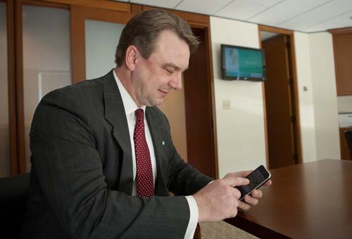ON THE GO: Citizens Financial Group's Steven Wooters shows off the bank's mobile-banking app on his iPhone. /