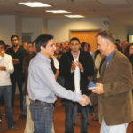 hooray for you: Staff applaud James McIlton, left, as he accepts a monthly recognition award from company President Kurt Noyce. Photo courtesy embrace home loans /