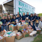 BANK ON IT: BankNewport President and CEO Thomas W. Kelly, back row center, Executive Vice President and COO Sandra J. Pattie, center, and company employees help load more than three-quarters of a ton of food donated during the bank's summer collection drive. /