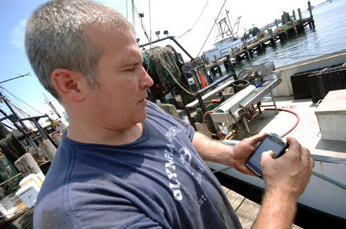 SPECIAL DELIVERY: Fisherman Stephen Arnold checks his smartphone to see what local restaurants need for their tables. / PBN PHOTO/BRIAN MCDONALD