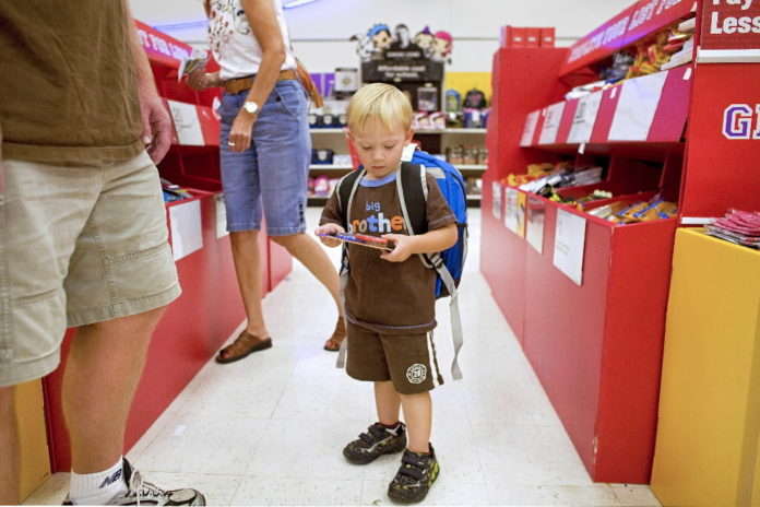 EVAN OLDS, 3, who is about to start preschool, wears a new backpack and looks at other school supplies while shopping with his father Rich at a Super Target store in Littleton, Colo. / BLOOMBERG NEWS FILE PHOTO/MATTHEW STAVER