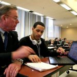 UP TO SPEED: Joe McNamara, left, principal of Pawtucket Alternative Learning Program, works with a student. Also a state representative, McNamara has proposed a statewide policy for online education. / PBN PHOTO/MICHAEL PERSSON