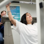 BODY AND HEALTH: Partridge Snow & Hahn employees Ellie Malloy, background, and Robin M. Kuznitz take advantage of the law firm's on-site gym to meet their fitness goals. / PBN PHOTO/RUPERT WHITELEY