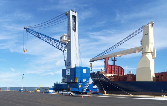 SWING INTO ACTION: The new mobile harbor crane, left, purchased by the Quonset Development Corporation, in use at the Port of Davisville. / COURTESY QUONSET DEVELOPMENT CORP.