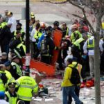 FIRST RESPONDERS TEND to the wounded where two explosions occurred along the final stretch of the Boston Marathon on Boylston Street in Boston on Monday. Two powerful explosions rocked the finish line area of the Boston Marathon near Copley Square and police said many people were injured. / BLOOMBERG PHOTO/KELVIN MA