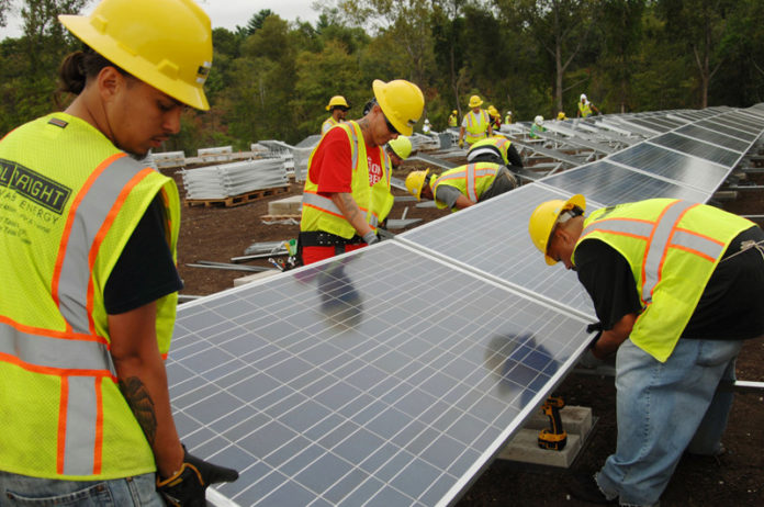 SHINING EXAMPLE: Workers install solar panels at East Providence Forbes Street project, due for completion in 2017. / PBN FILE PHOTO/BRIAN MCDONALD