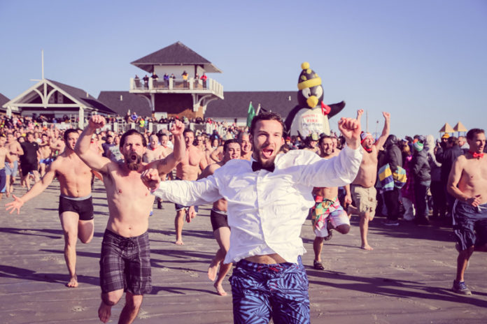 HUNDREDS OF PEOPLE take the plunge for Special Olympics Rhode Island on Jan. 1 at Roger Wheeler State Beach in Narragansett. The annual Penguin Plunge event has raised more than $2 million over three decades. / COURTESY KATIE LARSH