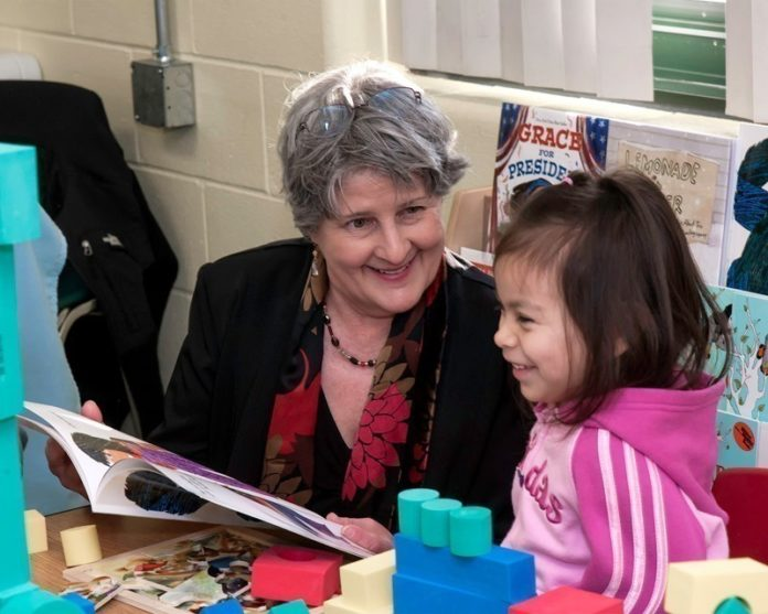 WORKING TOGETHER: Michelle Novello, program coordinator at the Providence Community Library, reads to Marelyn Colon, 5, of Providence. Novello's group's collaboration with two Providence nonprofits helped land a $250,000 grant last year. / PBN PHOTO/MICHAEL SALERNO