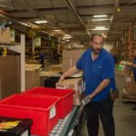 PACK, STACK AND GO: Banneker Industries employee Nick Vierira doing what the company does best at its North Smithfield warehouse: handling logistics, including packing and shipping, for third parties. / PBN PHOTO/TRACY JENKINS