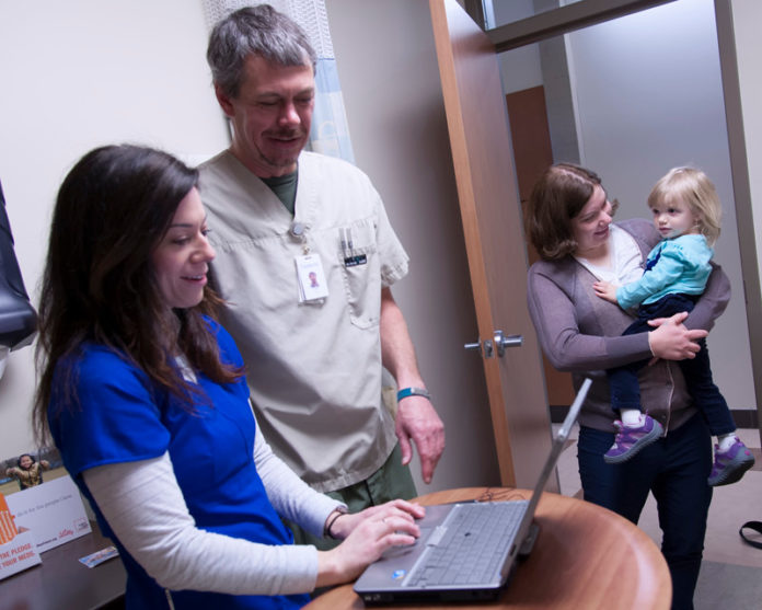 AMANDA ST. GEORGE, left, shadows nurse Todd Kirschhofer at Thundermist Health Center in West Warwick as part of the Passport to Practice program, designed to give unemployed or underemployed nurses experience and help finding a job. Also pictured are Valerie Furr and her mother, Karen Izzo. / PBN FILE PHOTO/MICHAEL SALERNO