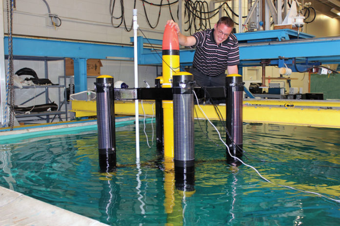 RIDING THE WAVE: Travis Tucker, an engineer at Electro Standards Laboratories, performs a preliminary in-water buoy testing for a project on wave-energy generation being done in collaboration with the University of Rhode Island. The test was done at the URI Bay Campus in Narragansett. / COURTESY ELECTRO STANDARDS LABORATORIES