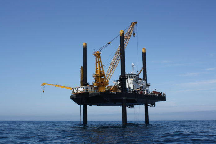 A LIFT BOAT OFF BLOCK ISLAND does geological sampling for Deepwater Wind's Block Island Wind Farm. At the time of this 2009 photo, the Louisiana-based company Montco Offshore, expected to begin installing wind turbines in 2013. So far, the 100-turbine Block Island Wind Farm is still in the permitting process. / COURTESY DEEPWATER WIND