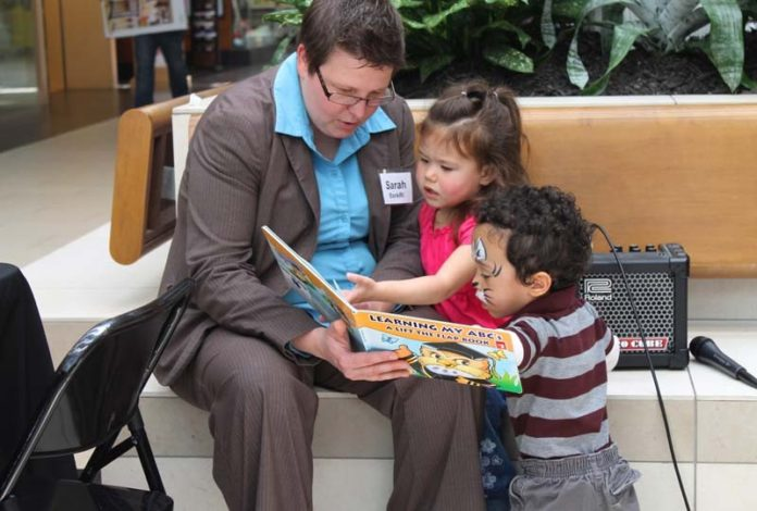 SARAH CLAUSIUS-PARKS, branch manager at Bank Rhode Island's Downtown Providence office, reads with two children during the literacy event at Warwick Mall.