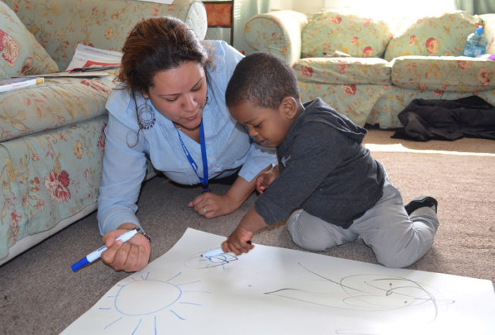 JENNIFER BONILLA of Providence's Meeting Street works with Elias Castillo to help him practice fine-motor skills and matching shapes through the Healthy  Families America Initiative.