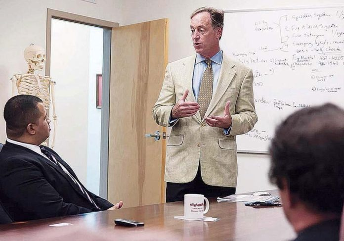 MATERIAL WORLD: John D. Jarrell, president of Materials Science Associates and founder of BioIntraface Inc., pictured above standing, speaks to associates about one of the company's products, a coated screw that promotes faster healing in bone-fracture repair. / PBN PHOTO/ MICHAEL SALERNO