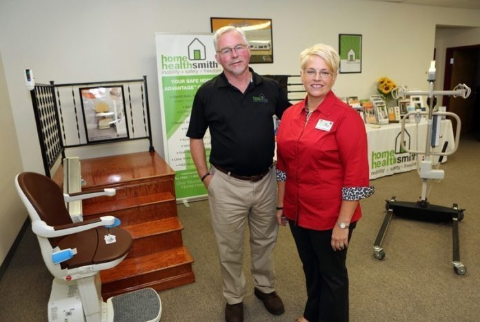 HOME AGAIN: Bill and Linda Bohmbach demonstrate a stair lift in the showroom at their Portsmouth company, Home Healthsmith. In two years the company, which provides adaptive mobility equipment, has grown from a home-based business to a 5,000-square-foot facility with five employees. / PBN FILE PHOTO/KATE WHITNEY LUCEY