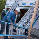 FRUITS OF LABOR: While the overall construction-labor market hasn't entirely rebounded, there are growing demands in certain specialty areas. Above, Picerne Homes vinyl-siding installers Hugo Caal, foreground, and Jose Alfredo Garcia work on a home in Cranston. / PBN PHOTO/MICHAEL SALERNO