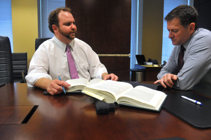 PREP WORK: State Rep. Cale Keable, D-Burrillville, co-chairman of the Bi-Partisan Preparatory Commission for a Constitutional Convention, left, speaks with Michael Gamboli, a partner at Partridge Snow and Hahn LLP. / PBN PHOTO/FRANK MULLIN