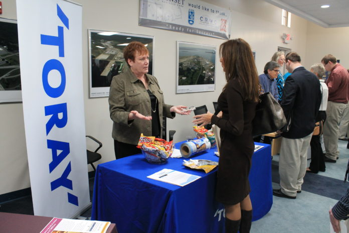 FEVER PITCH: Peg Lamere, Senior Recruiter with Toray Plastics (America) Inc., a tenant at Quonset Business Park, discusses job opportunities with Diane Miceli of North Kingstown. / COURTESY QUONSET DEVELOPMENT CORPORATION