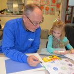 HOLIDAY GIVING: Peter Campbell, from Blue Cross & Blue Shield of Rhode Island's communications department, volunteers his time at Meeting Street in Providence, working with Georgia, a pre-K student. / COURTESY BCBSRI