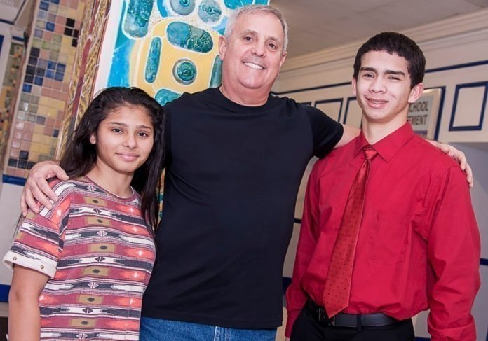 "IDENTIFYING 'GOOD KIDS': Norman Kelly, Metta Students Foundation founder, with Blanca Colato, left, and Justin Crespo, who received $1,000 grants from the nonprofit for engaging in an ""act of kindness."" / PBN PHOTO/MICHAEL SALERNO"