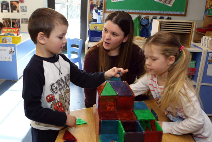 MAKING THE MOST: Child and Family Services substitute child care worker Sarah Murphy of North Kingstown works with children. The junior at Rhode Island College is seeing an increase in her minimum-raise pay. / PBN PHOTO/KATE WHITNEY LUCEY