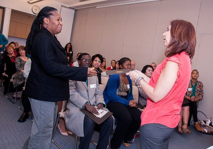 IN STRIDE: Joan Pierre, left, receives a certificate from Stepping Up career adviser and community liaison Erin Cheschi at a graduation ceremony at Women & Infants Hospital. Twenty-one students graduated from the Healthcare Career Orientation Program. / PBN PHOTO/MICHAEL SALERNO