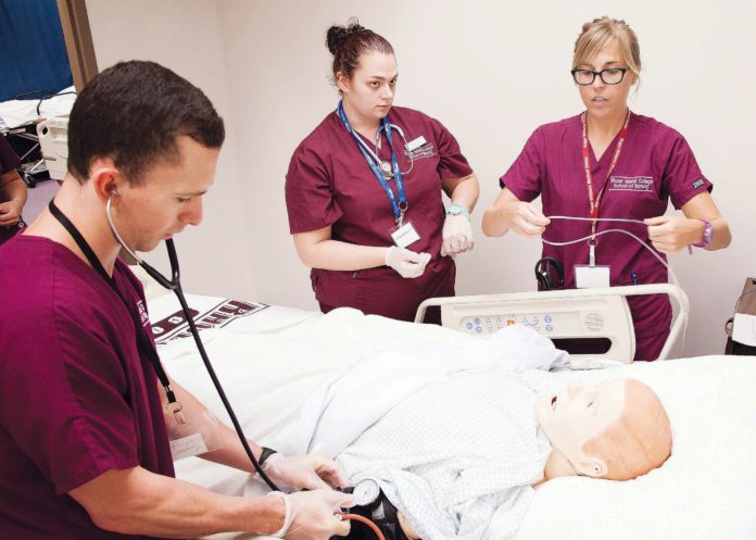SIM CITY: Rhode Island College nursing students, from left, Andrew Sharpe, Heather Us-Spaziano and Amy Schnabel, train in the SIM lab. / COURTESY ?EUGENE ?ST. PIERRE
