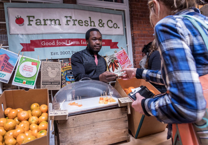 HOME GROWN: Osbert Duoa, a sales manager at Farm Fresh Rhode Island, works at the Pawtucket Wintertime Farmers Market in the Hope Artiste Village in 2015. / PBN FILE PHOTO/MICHAEL SALERNO