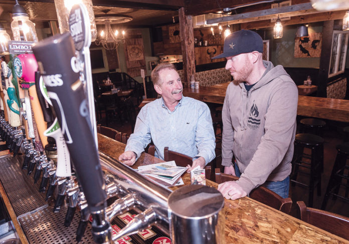 READY TO EAT: David Rosenberg, left, owner of Newport County Dinner Club, meets with the owner of The Wharf Pub, Scott Kirmil. Rosenberg continues to sign up renewals and add new members to the club. / PBN PHOTO/MICHAEL SALERNO