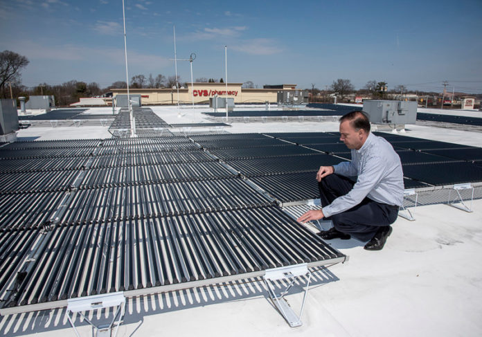 BRIGHT IDEA: Christopher Morra Sr., president and CEO of National Security, shows off a solar panel system that he said in 2014 had saved the company $8,631 in 13 months. / PBN FILE PHOTO/MICHAEL SALERNO