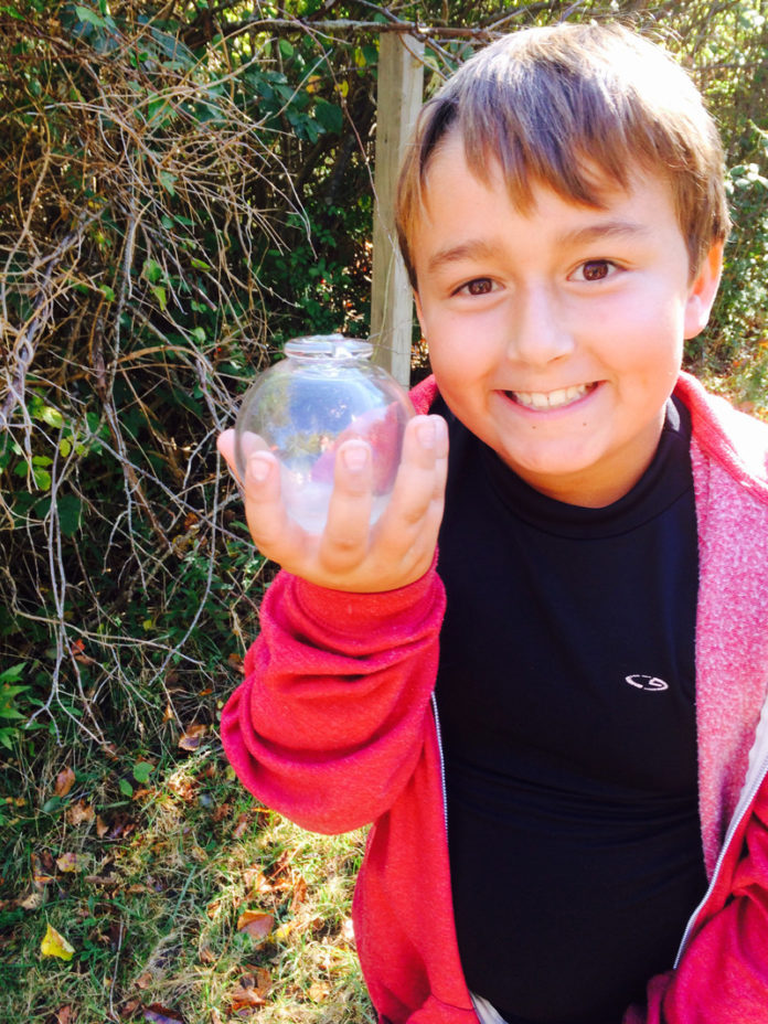 CLEAR AS DAY: Auggie Lambert shows off one of the glass floats made by Eben Horton. / COURTESY JENNIFER SEEBECK LAMBERT