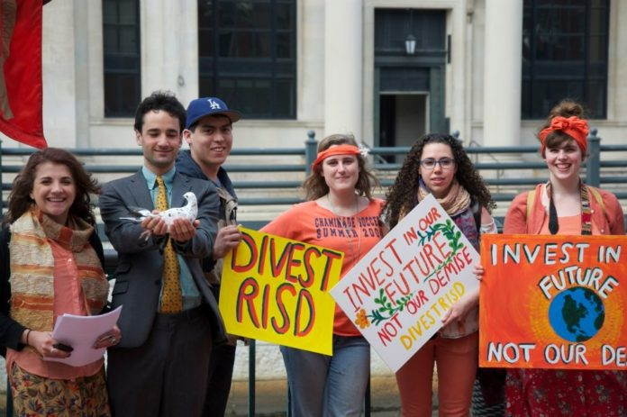 RHODE ISLAND SCHOOL OF DESIGN STUDENTS hold signs urging RISD to divest in this photograph posted on Facebook. The Board of Trustees recently voted to divest its direct investments in fossil-fuel extraction company stocks and bonds, after a two-year study. / COURTESY DIVEST RISD CAMPAIGN