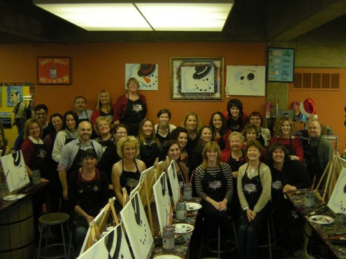 IN THE SPIRIT: Healthcentric Advisors staff celebrate the holiday season with a Paint and Soda Party. / COURTESY HEALTHCENTRIC ADVISORS