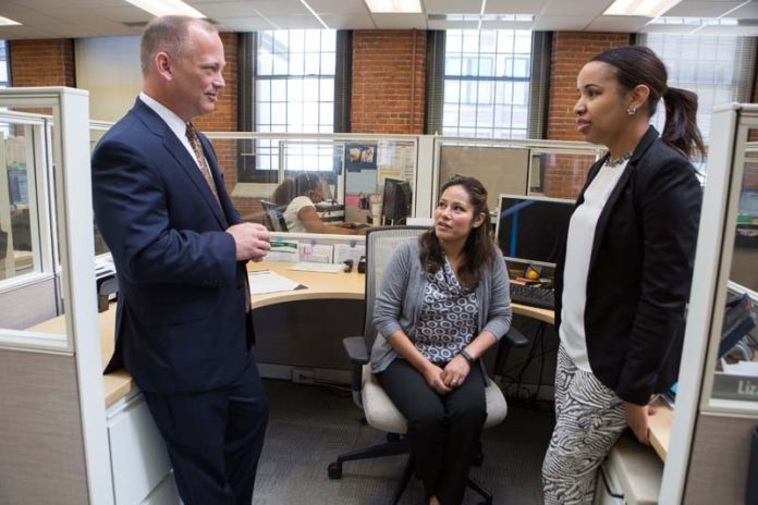 GOOD NEIGHBORS: Neighborhood Health Plan of Rhode Island saw its revenue jump in 2014 to $829.6 million from $427.6 million in 2012. Above, CEO Peter Marino speaks with Telma Gonzalez, center, and Lizzy Lima. / PBN PHOTO/RUPERT WHITELEY