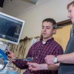 A NEW SURGICAL PATH: Raynham-based Medrobotics' flexible robotic surgical device, being demonstrated by mechanical engineer Ian Darisse, left, and biomedical engineer Rich Kuenzler, allows surgeons better access to body parts. / PBN PHOTO/MICHAEL SALERNO