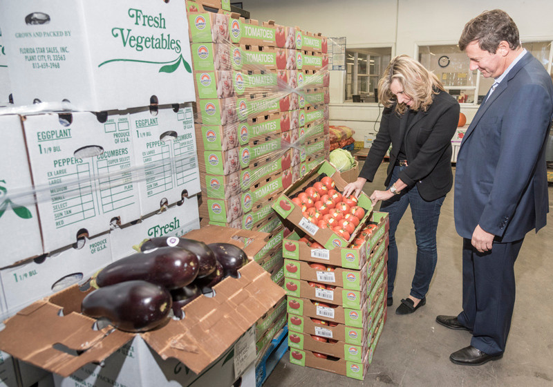 FRUIT OF THEIR LABOR: Steven Sigal and his sister, Jamie Manville, along with their brother, Andrew Sigal, not pictured, are co-owners of Tourtellot & Co. Inc., a Warwick fruit and vegetable distributor. Steven and Jamie are looking at the produce on the floor of the warehouse. / PBN PHOTO/MICHAEL SALERNO